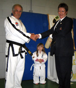Master Howard presents Ms Keane with 6th Degree Black belt cert